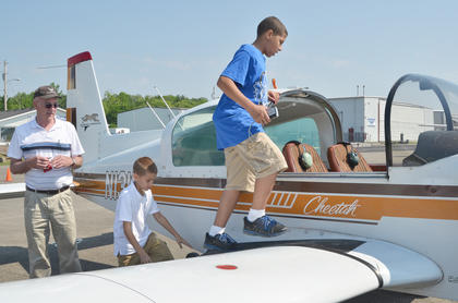 Sheray Gaines, center, and his brother, Chaz Cave, both of Campbellsville, climb aboard for a plane ride. Pilot Edward Jett of Elizabethtown is at left.