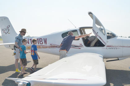 Chris Gibbs of Campbellsville, at left, helps his son, J.P., and Michael J. Todd into a place for a ride. In middle is airport staff member Donnie Pike holding the plane door open.