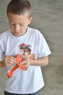 Kadyn Grady of Campbellsville plays with a paper airplane at Saturday's fly-in after riding in a real plane.