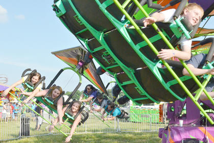 Fairgoers smile as they fly high in the air on a midway ride.