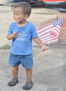 Gavin Humphress, 23 months, of Campbellsville, waves an American flag as he walks down Main Street with his mother.