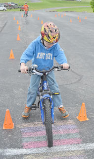 Collin Moore, 7, of Campbellsville, sees how well he can stop his bicycle during the rodeo competition.