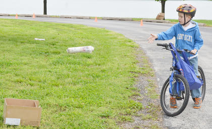 Collin Moore, 7, of Campbellsville sees how well he can ride a bicycle and deliver newspapers at the same time.