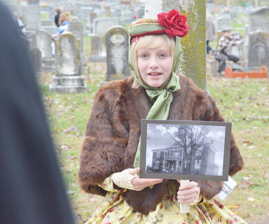 Molly Sullivan portrays the ghost of Maggie Mayes Hoskins. Here, Sullivan shows the crowd the home Hoskins lived in.