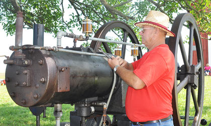 Ron Arnett of the Grab community in Green County prepares to show the power behind his 100-year-old South-Penn Oil field engine at the Russell Creek/Homeplace on Green River Antique Gas Engine and Tractor Show on Saturday.