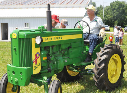 Wayne Livesay of Campbellsville chats with spectators about his 1957 John Deere Model 320 tractor at the Russell Creek/Homeplace on Green River Antique Gas Engine and Tractor Show on Saturday.