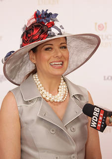 Actress Debra Messing does an interview as she walks the red carpet at the Kentucky Derby.