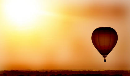 The sun rises behind a hot air balloon above Campbellsville before the city&#039;s Fourth of July festivities begin.