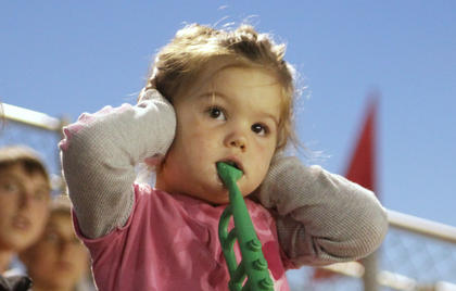 Zoe Cash, 3, covers her ears from the noise of the truck pull at the fair.