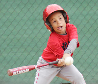 Keshawn Smith of the Red Sox makes contact with a pitch in pee wee action against the Cubs.
