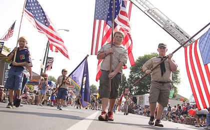 Local Cub Scouts and Boy Scouts carry flags during the Fourth of July parade.