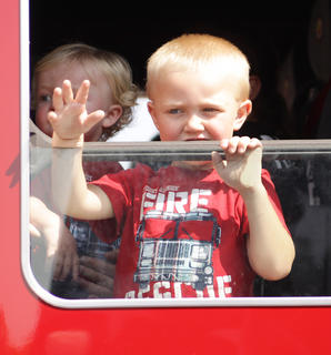 A young boy waves to the crowd from a fire truck during the Fourth of July parade.