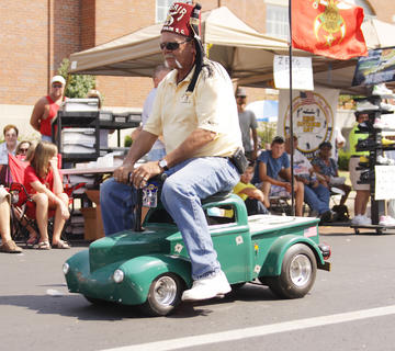 Members of the Kosair Mark Twain Shrine Club entertain the crowd during the Fourth of July parade, driving miniature classic hot rods.