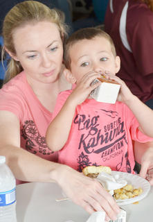 Valerie Dykes of Campbellsville holds her son, Landon, as he drinks milk at this year's free breakfast on Thursday morning at Campbellsville Christian Church. The breakfast was the only event rain didn't cancel on Thursday.