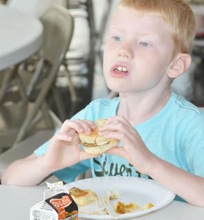 Colton Dykes, 6, of Campbellsville, takes a bite of a sausage biscuit at the breakfast.