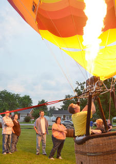 Campbellsville residents watch as hot air balloonists inflate a balloon at Taylor County High School on Wednesday night. Though balloonists weren't able to provide tethered rides, residents were still able to sit inside the balloons and see them glow.