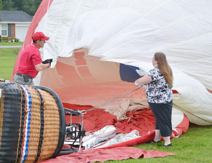 Balloonists work to inflate the National Guard hot air balloon. Though balloonists weren't able to provide tethered rides on Wednesday night, residents were still able to sit inside the balloons and see them glow.