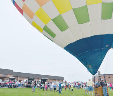 Campbellsville residents gather at Taylor County High School on Wednesday night to see hot air balloons. Though balloonists weren't able to provide tethered rides, residents were still able to sit inside the balloons and see them glow.