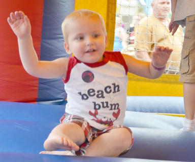 Lucas Anderson, 2, of Campbellsville, jumps in an inflatable house at the Family Fun Zone on Wednesday.