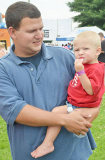 Matthew Harris of Campbellsville holds his son, Noah, 18 months, as he takes one of his first bites of cotton candy at the Family Fun Zone.