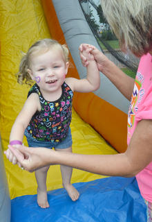Margo Sanders of Elk Horn Baptist Church, which, along with Living Grace Church, hosted the annual Family Fun Zone, helps Aubri Dobson, 2, of Campbellsville, bounce after she slid down an inflatable slide.