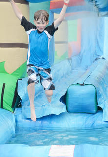 Eli Pyles of Wilmore, Ky., splashes on a slide at the Family Fun Zone on Wednesday night.