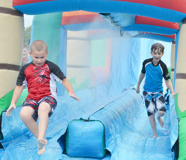 Jacob Skaggs of Campbellsville, at left, and Eli Pyles of Wilmore, Ky., slide down an inflatable slide at the Family Fun Zone on Wednesday night.