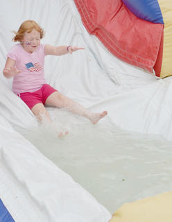 Kaylei Sammons, 5, of Campbellsville, smiles as she splashes on a slide at the Family Fun Zone on Wednesday night.