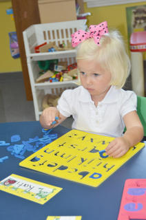 Kati Wilson, a student in the Sonbeams class, works on an ABCs puzzle.