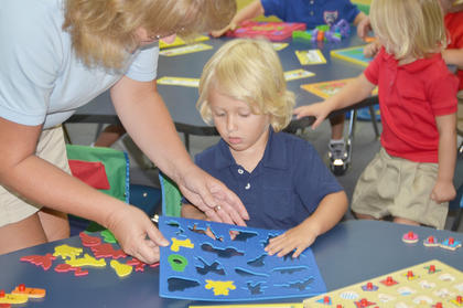 Sonbeams teacher Tanya Massengale helps Griffin Hansford with a shapes puzzle.