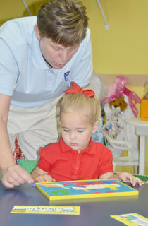 KCA Administrator Lori Eubank helps Sonbeams student Braylee Mackie with a puzzle just after the start of school.