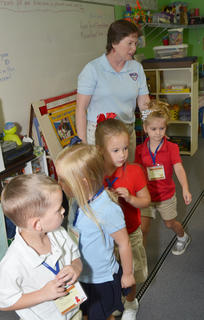 KCA preschool teacher Melinda Gray teaches her students how to line up to leave the classroom.