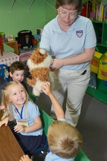 KCA preschool teacher Melinda Gray shows her students Max the dog, a puppet that will help them learn throughout the year.