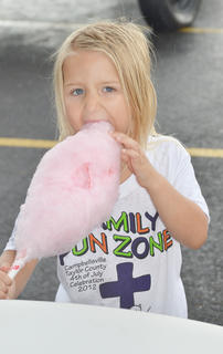 Loralei Graham, 5, of Campbellsville, takes a big bite of cotton candy at the Family Fun Zone.