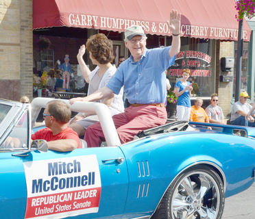 U.S. Sen. Mitch McConnell, R-Ky., waves to the crowd during the parade.
