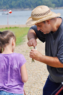 Faith Moore, 7, gets help from her dad Brian when she reels in a fish at Green River Lake.
