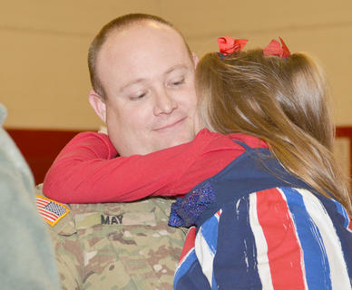 Staff Sgt. Travis May, who was recently sworn in as a Bradfordsville City Commissioner and has been deployed to the Middle East, hugs his daughter, Halee, after Friday&#039;s ceremony.