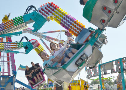 Children, teenagers and adults alike enjoy riding the midway rides, like the Orbiter, at the fair.