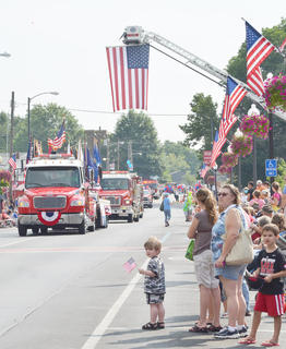 Taylor Countians celebrated their freedom on Friday, July 12, and Saturday, July 13, with hot air balloons, music, food, fireworks and a parade. The community's annual Fourth of July celebration was rescheduled after rain canceled the day's events. Above, children and adults raise their American flags as fire trucks make their way down Main Street in Saturday's parade.
