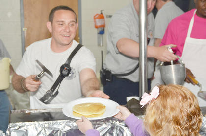 Keith Bricken serves pancakes to Chloe Motheral of Campbellsville.