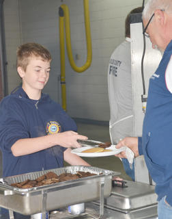 Josh Dooley serves sausage on Saturday morning.