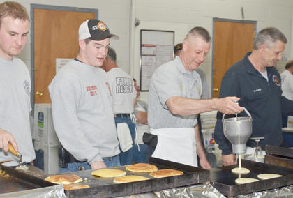 From left, Alex Quinn, Nick Penick, Campbellsville Fire & Rescue Chief Kyle Smith and Dennis Curry cook pancakes.