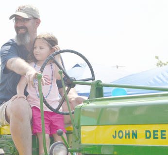 This year&#039;s parade featured several tractors, many with children aboard.