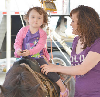 Brittany Cox guides Anna Keith for a ride on a pony at the fair&#039;s petting zoo. Both are from Campbellsville.