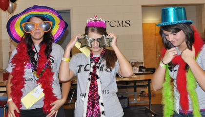 From left, Emily White, Erika Gaddie and Mariah Malone decide what to wear in the photo booth at TCHS Project Graduation on May 24.