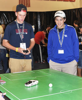 John Eastridge, right, watches as Justin Hazel tries to keep the ball on the field as he plays SocCar at TCHS Project Graduation on May 24.