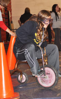 April Biggs knocks some cones over as she pedals her tricycle through the obstacle course at TCHS Project Graduation on May 24.