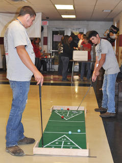 Brandon Holt, left, watches as opponent Dylan Skaggs tests his golf skills while playing shuffle putt at TCHS Project Graduation on May 24.
