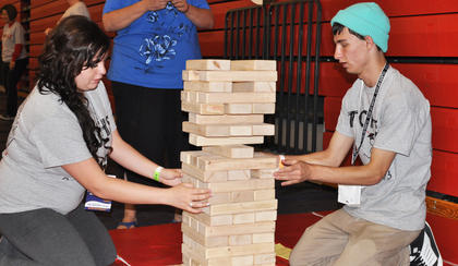 Ariel Paris and Jonathan Walters stay in sync as they gingerly slide blocks out of the giant Jenga tower at TCHS Project Graduation on May 24.
