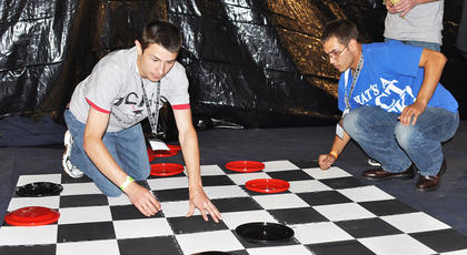Justin Ronna prepares to slide a checker across a giant checkerboard as opponent Orrin Wooley contemplates his next move at TCHS Project Graduation on May 24.